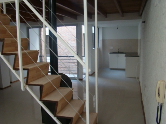 Staircase and woodstove, looking toward the kitchen (right) and balcony (left)