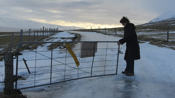 Bronwyn gingerly operates a farm gate on treacherous footing