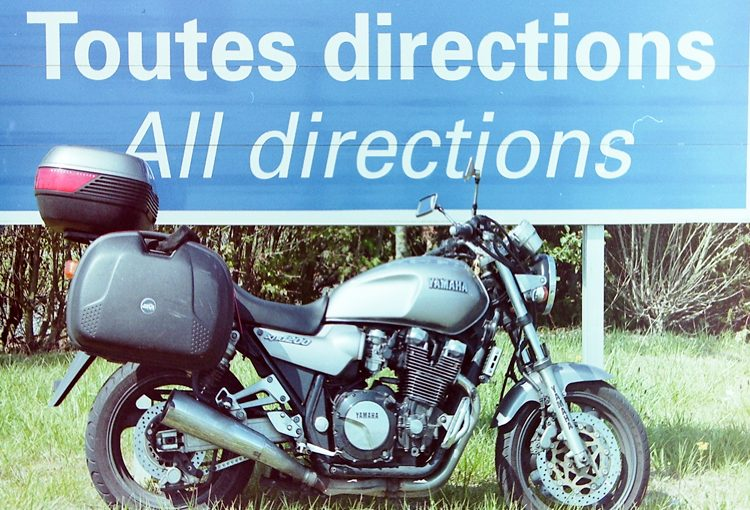 "Motorcycle and ""Toutes Directions"" sign"